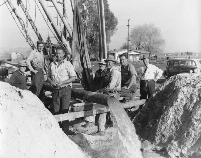 Men gathered around water drilling rig.