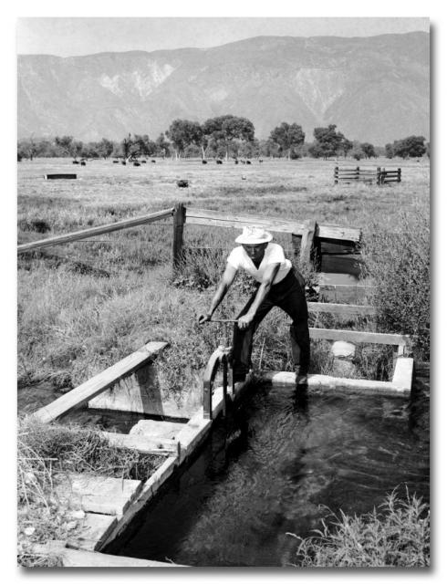 Farmland irrigation canal with farmer opening gate to divert water.